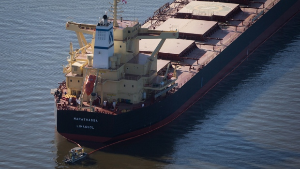 A spill response boat monitors a boom placed around the bulk carrier cargo ship Marathassa after a bunker fuel spill on Burrard Inlet in Vancouver, on Thursday, April 9, 2015. (Darryl Dyck / THE CANADIAN PRESS)