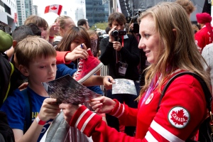 Olympic Gold medalist Rosie MacLennan (right) signs an autograph for a young fan following Canada's Olympic Committee's parade in Toronto on September 21 2012 to mark the country's performance in the London 2012 Olympics. (Chris Young / The Canadian Press)