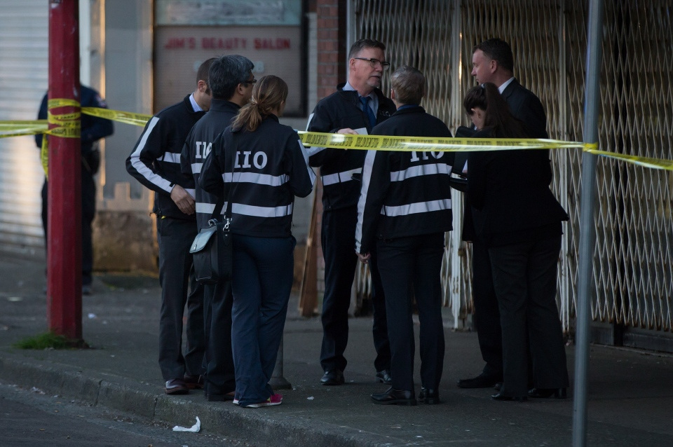Members of the Independent Investigations Office of BC (IIO) talk at the scene where a Vancouver Police officer shot and killed a man who allegedly stabbed three people in the Downtown Eastside of Vancouver, Thursday, April 9, 2015. (Darryl Dyck / THE CANADIAN PRESS)