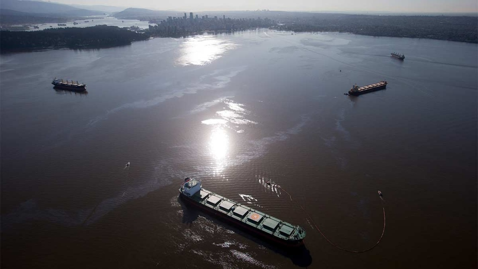 Crews on spill response boats work to contain bunker fuel leaking from the bulk carrier cargo ship Marathassa, second right, on Burrard Inlet in Vancouver, on Thursday, April 9, 2015. (Darryl Dyck / THE CANADIAN PRESS)