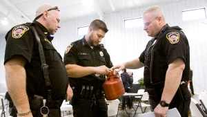 Indiana police officers study a biohazard container for the disposal of needles at an HIV-AIDS training session in Austin, Indiana, on April 1, 2015. (News and Tribune/Christopher Fryer)