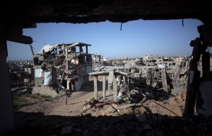 A Palestinian girl walks next to destroyed houses, in the Shijaiyah neighborhood of Gaza City, on Monday, March 30, 2015. (AP / Khalil Hamra)