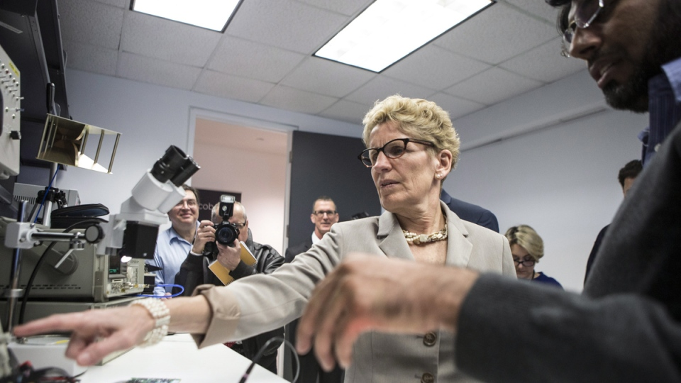 Ontario Premier Kathleen Wynne visits a lab at Ecobee, which produces Wi-Fi controlled domestic thermostats, before an announcement which outlined a cap and trade deal with Quebec aimed at curbing greenhouse emissions, in Toronto on Monday, April 13, 2015. (Chris Young / THE CANADIAN PRESS)