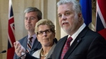 In this file photo, Quebec Premier Philippe Couillard, right, speaks at a news conference following a meeting with Ontario Premier Kathleen Wynne, at the premier's office in Quebec City, Monday, April 13, 2015. (Jacques Boissinot / THE CANADIAN PRESS)