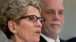 Ontario Premier Kathleen Wynne, left, speaks at a news conference following a meeting with Quebec Premier Philippe Couillard, right, Monday, April 13, 2015 at the premier's office in Quebec City. (Jacques Boissinot / THE CANADIAN PRESS)