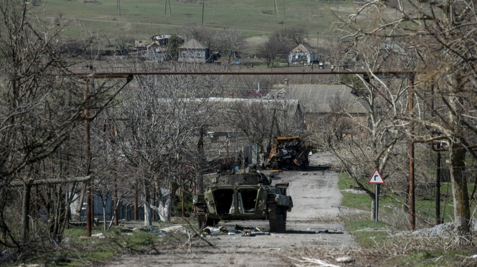 A damaged armed vehicle of Pro-Russian rebels stands between the positions of Pro-Russian rebels and Ukrainian army in Shyrokyne village, eastern Ukraine on April 10, 2015. (AP / Evgeniy Maloletka)