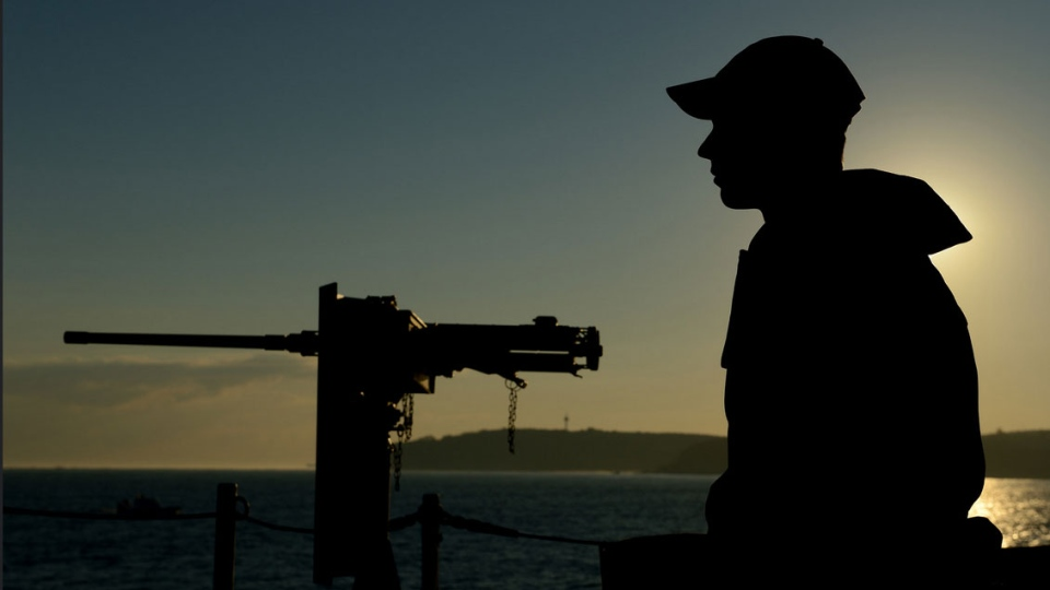 As the sun rises, a member of the ship's company on board HMCS Toronto provides force protection while transiting through the Bosphorus Strait during Operation Reassurance, the mission to support NATO in Central and Eastern Europe, Sept. 25, 2014. (Sgt. Matthew McGregor / Canadian Forces Combat Camera)