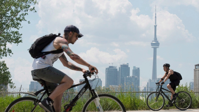 Cyclists ride past the skyline in Toronto on Wednesday, June 26, 2012. (The Canadian Press/Frank Gunn)