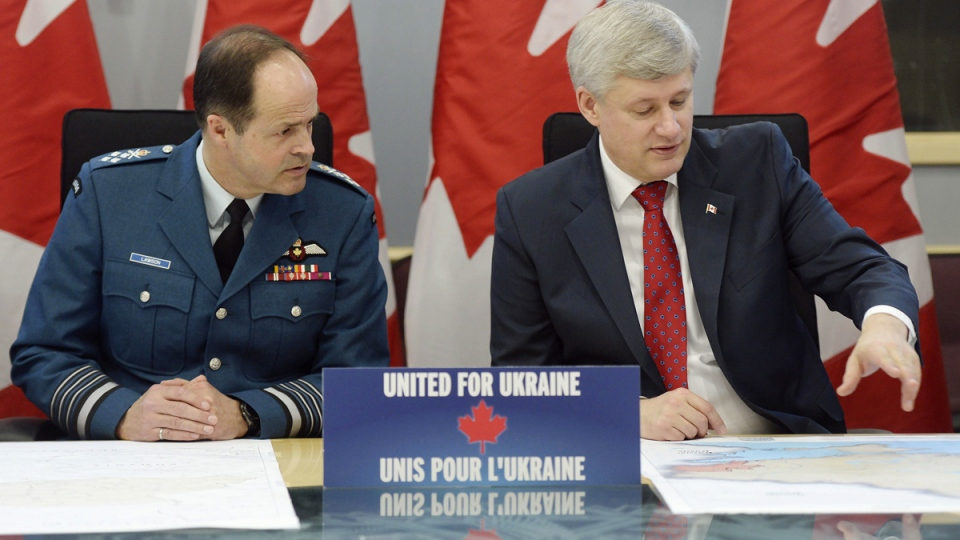 Prime Minister Stephen Harper, right, and General Thomas Lawson, Chief of the Defence Staff, talk before making an announcement in Ottawa on Tuesday, April 14, 2015. (Adrian Wyld / THE CANADIAN PRESS)