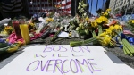 Flowers and signs adorn a barrier, two days after two explosions killed three and injured hundreds, at Boylston Street near the of finish line of the Boston Marathon at a makeshift memorial for victims and survivors of the bombing on April 17, 2013. (AP / Charles Krupa)