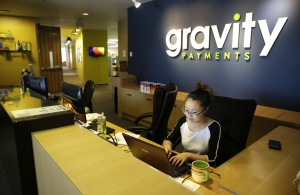 An employee works at the front desk of Gravity Payments in Seattle on Apr. 15, 2015. (AP / Ted S. Warren)