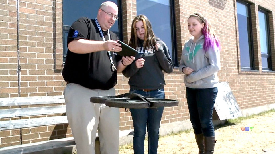Teacher Benjamin Kelly shows students Alyson Furness (middle) and Carrie Lafford (right) how to fly a drone at Caledonia Regional High School in Hillsborough, N.B., on Apr. 16, 2015.