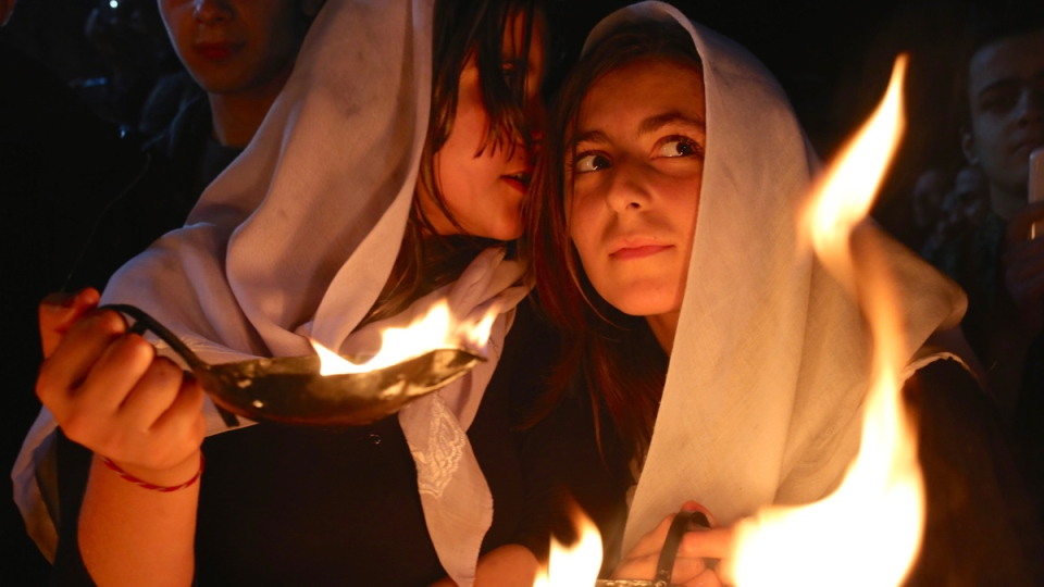 A Yazidi woman whispers into the ear of her friend as both hold small fires to make a wish for the Yazidi new year, at the holy shrine of Lalish, 57 kilometres north of the militant-held Mosul, Iraq, Tuesday, April 15, 2015. (AP / Bram Janssen)
