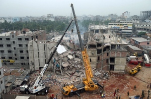 In this April 29, 2013 file photo, the collapsed Rana Plaza garment factory building is seen from a building nearby as a crane prepares to lift the fallen ceiling in Savar, near Dhaka, Bangladesh. (Wong Maye-E / AP Photo)