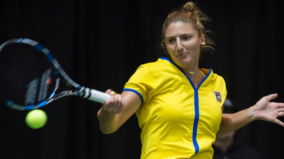 Romania's Irina-Camelia Begu returns the ball to Canada's Francoise Abanda during Federal Cup tennis action in Montreal, Saturday, April 18, 2015. THE CANADIAN PRESS/Graham Hughes