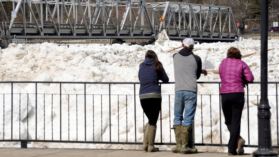 People check out the ice jammed around the bridge crossing the St. John River in the Village of Perth-Andover on Sunday, April 19, 2015. (Stephen MacGillivray / THE CANADIAN PRESS)