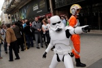 A man dressed as a Stormtrooper poses for photographers next to people queuing to attend the steaming of Star Wars Celebration from the Anaheim Convention Center in California, in Paris, France, Thursday, April 16, 2015. (AP Photo/Christophe Ena)