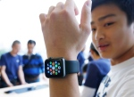 A customer tries on an Apple Watch at an Apple Store in Hong Kong Friday, April 10, 2015.(AP Photo/Kin Cheung)