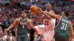 Chicago Bulls guard Jimmy Butler is fouled by Milwaukee Bucks centre John Henson as Jared Dudley watches during the second half in Game 2 of the NBA basketball playoffs on April 20, 2015, in Chicago. (AP / Charles Rex Arbogast)