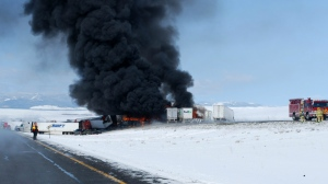 In this photo provided by the Wyoming Highway Patrol smoke rises following the aftermath of a chain-reaction crash along Interstate 80 near Laramie, Wyo. on April 20, 2015. (Wyoming Highway Patrol)