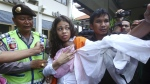 Heather Mack of Chicago, Ill., centre, carries her baby daughter as she arrives at the Denpasar District Court before her verdict trial in Bali, Indonesia, on April 21, 2015. Mack and her boyfriend Tommy Schaefer were given prison sentences in the murder of Mack's mother. (AP / Firdia Lisnawati)