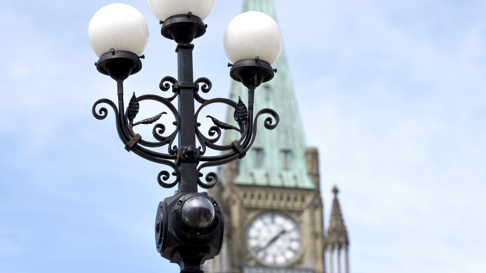 A CCTV surveillance camera is shown with Centre Block's Peace Tower on Parliament Hill in Ottawa on Tuesday, April 21, 2015. (Justin Tang / THE CANADIAN PRESS)
