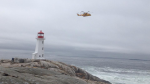 A search-and-rescue helicopter searches the waters off Peggys Cove after a man fell off the rocks.