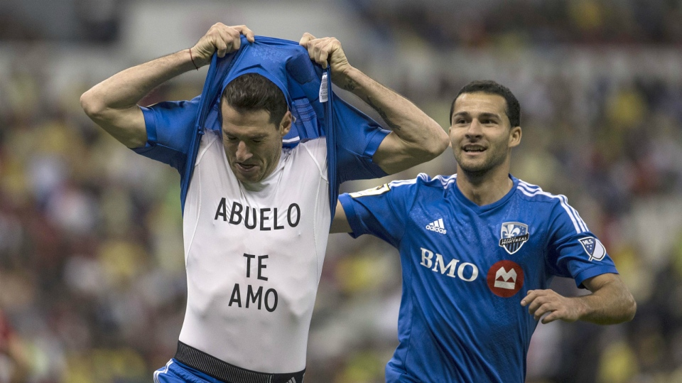 Ignacio Piatti of Canada's Montreal Impact celebrates scoring a goal against Mexico's America by showing his undershirt with the message that reads in Spanish 'Grandfather I love you' as teammate Dilly Duka, right, runs behind him during a CONCACAF Champions league match in Mexico City on April 22, 2015. (AP / Christian Palma)