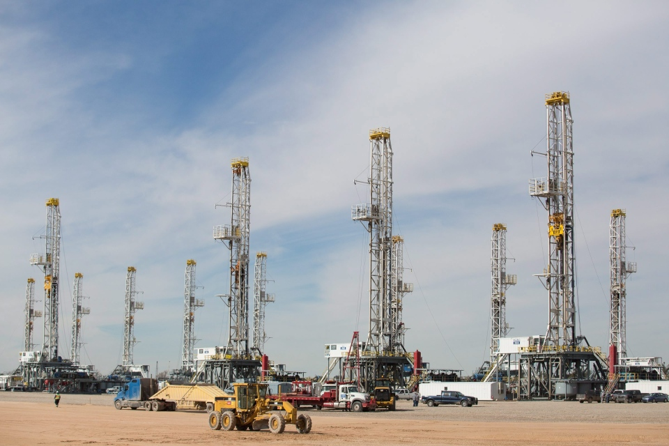 This Monday, Jan. 26, 2015 photo shows a number of idle oil drilling rigs in Helmerich & Payne International Drilling Company's yard in Ector County, Texas. (Odessa American / Courtney Sacco / AP Photo)