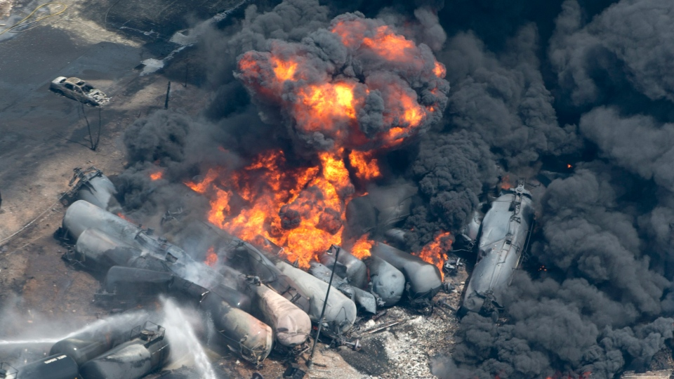 Smoke rises from railway cars that were carrying crude oil after derailing in downtown Lac Megantic, Quebec, July 6, 2013. (Paul Chiasson / THE CANADIAN PRESS)