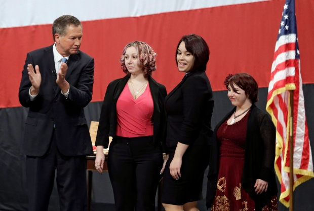This Monday, Feb. 24, 2014 file photo shows Ohio Gov. John Kasich, from left, introducing Amanda Berry, Gina DeJesus and Michelle Knight during his State of the State address at the Performing Arts Center in Medina, Ohio. Berry broke through a screen door to freedom last May.(AP Photo/Tony Dejak, File)