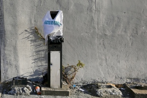 A T-shirt made in memory of Freddie Gray is draped over former pay phone post near the intersection where Gray was arrested on Friday, April 24, 2015, in Baltimore. Gray died from spinal injuries about a week after he was arrested and transported in a police van. (AP / Patrick Semansky)