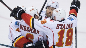 Calgary Flames' Kris Russell, from left to right, Dennis Wideman, David Jones and Matt Stajan celebrate Jones' goal against the Vancouver Canucks during the first period of game 5 of an NHL Western Conference first round playoff hockey series in Vancouver, B.C., on Thursday April 23, 2015. (Darryl Dyck / THE CANADIAN PRESS)