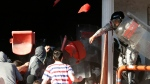 A Serbian riot police officer clashes with Red Star fans during a Serbian National soccer league derby match between Red Star and Partizan, in Belgrade, Serbia, Saturday, April 25, 2015. (AP / Darko Vojinovic)