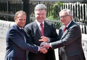 Ukrainian President Petro Poroshenko, center, joins hands with European Council President Donald Tusk, left, and European Commission President Jean-Claude Juncker, ahead of a EU-Ukraine summit, in Kiev, Ukraine, Monday, April 27, 2015. (AP / Efrem Lukatsky)