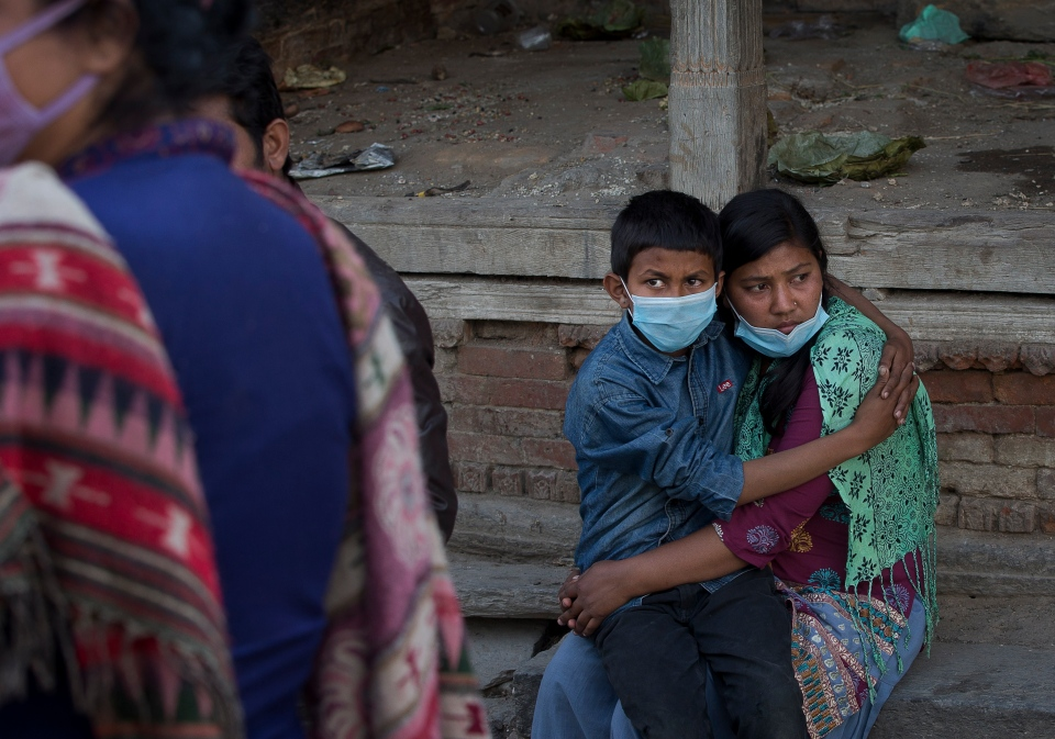 Monika Basnet, 15, right, holds her brother Munal Basnet, 10, during the cremation of their father killed in Saturday's earthquake, at the Pashupatinath temple, on the banks of Bagmati river, in Kathmandu, Nepal, Monday, April 27, 2015. (AP / Manish Swarup)