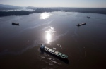 Crews on spill response boats work to contain bunker fuel leaking from the bulk carrier cargo ship Marathassa, second right, on Burrard Inlet in Vancouver, B.C., on April 9, 2015. (Darryl Dyck / The Canadian Press)