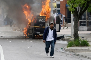 A man walks past a burning police vehicle, Monday, April 27, 2015, during unrest following the funeral of Freddie Gray in Baltimore. (Patrick Semansky / AP Photo)