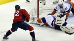Washington Capitals centre Evgeny Kuznetsov shoots the game winning goal against New York Islanders goalie Jaroslav Halak and defenceman Johnny Boychuk during the third period of Game 7 in the first round of the NHL hockey Stanley Cup playoffs in Washington on April 27, 2015. (AP / Alex Brandon)