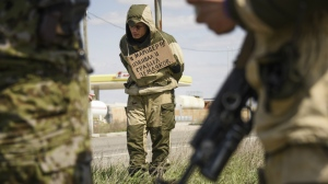 A man stands tied to a post by pro-Russian rebels, accused of stealing from local people, with a poster around his neck standing next to a highway in Krasnyi Partyzan, Ukraine, on April 23, 2015. (AP / Mstyslav Chernov)