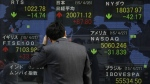 A man looks at an electronic stock board of a securities firm in Tokyo, Tuesday, April 28, 2015. Asian stock markets were lukewarm Tuesday, taking a cue from losses on Wall Street ahead of earnings from major Asian companies and the Federal Reserve's policy meeting. (AP / Eugene Hoshiko)