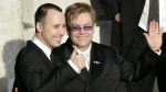 Elton John, right, and his longtime partner David Furnish, embracing as they wave to members of the media and the public after they had a civil ceremony at the Guildhall in Windsor, England on Dec. 21, 2005. (AP / Lefteris Pitarakis)