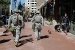 Maryland National Guardsmen pass a woman walking dogs in the Harbor East neighborhood of Baltimore, Tuesday, April 28, 2015, a day following unrest that occurred after Freddie Gray's funeral. (AP / Patrick Semansky)