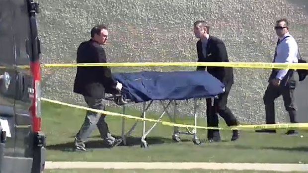 Officials remove one of the three bodies discovered inside a Lethbridge townhouse