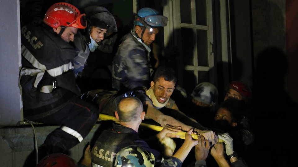 Survivor Rishi Khanal, 27, is freed by French rescuers from the ruins of a three-story hotel in the Gangabu area of Kathmandu, Nepal on April 28, 2015. (AP / Niranjan Shrestha)