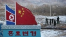 Chinese paramilitary policemen build a fence near a concrete marker depicting the North Korean and Chinese national flags with the words 'China North Korea Border' at a crossing in the Chinese border town of Tumen in eastern China's Jilin province on Dec. 8, 2012. (AP / Ng Han Guan)