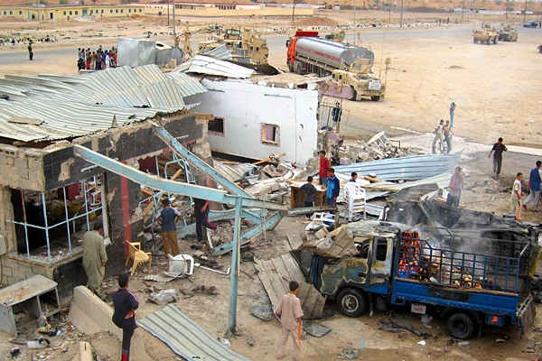 Local Iraqis inspect the damage caused by a suicide bomber attack on a highway near Ramadi, 115 kilometers (70 miles) west of Baghdad, Iraq, Monday, April 23, 2007. (AP Photo)