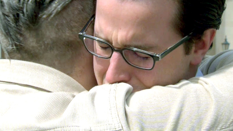 Mike Richey and Mark Henick hug while meeting in Toronto 12 years after Richey saved Henick's life, on Thursday, April 30, 2015.