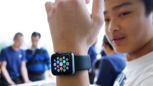 In this April 10, 2015, photo, a customer tries on an Apple Watch at an Apple Store in Hong Kong. (AP / Kin Cheung, File)
