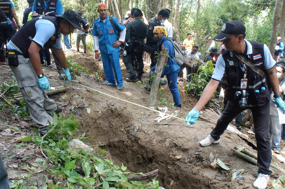 Thai police officials measure a shallow grave in Padang Besar, Songkhla province, in southern Thailand on Saturday, May 2, 2015. Police officials in Thailand trekked into the mountains to dig up shallow graves Saturday, after the grim discovery of an abandoned jungle camp renewed calls for a crackdown on the human trafficking networks operating in the Southeast Asian country. (AP / Sumeth Panpetch)